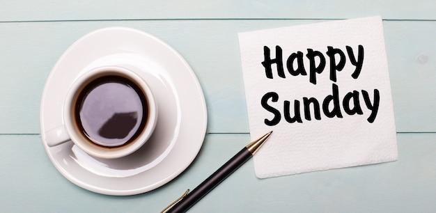 Na jasnoniebieskiej drewnianej tacy stoi biała filiżanka kawy, rączka i serwetka z napisem happy nunday.