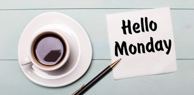 Na jasnoniebieskiej drewnianej tacy stoi biała filiżanka kawy, rączka i serwetka z napisem hello monday.