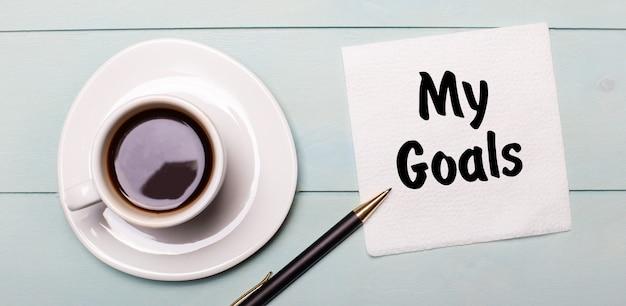Na jasnoniebieskiej drewnianej tacy stoi biała filiżanka kawy, rączka i serwetka z napisem moje cele