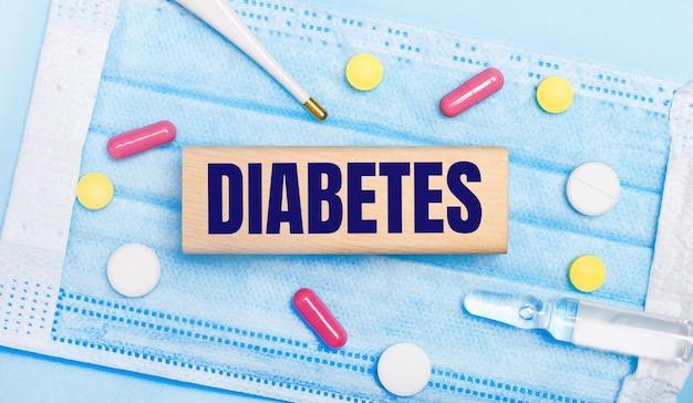 Na jasnoniebieskiej jednorazowej masce na twarz znajdują się tabletki, termometr, ampułka i drewniany klocek z napisem cukrzyca. koncepcja medyczna