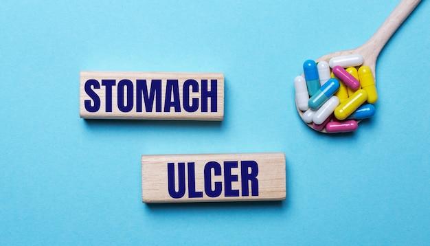Na jasnoniebieskiej powierzchni, jasne wielokolorowe pigułki w łyżeczce i dwa drewniane klocki z napisem stomach ulcer
