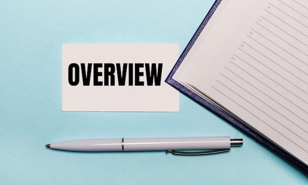 Na jasnoniebieskiej powierzchni otwarty notes, biały długopis i karteczka z napisem przegląd. widok z góry