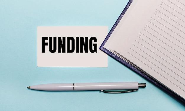 Na jasnoniebieskiej powierzchni otwarty zeszyt, biały długopis i karteczka z napisem finansowanie. widok z góry