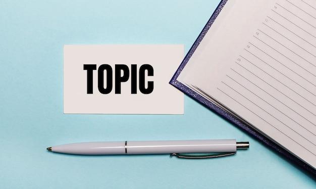 Na jasnoniebieskiej powierzchni otwarty zeszyt, biały długopis i karteczka z napisem topic