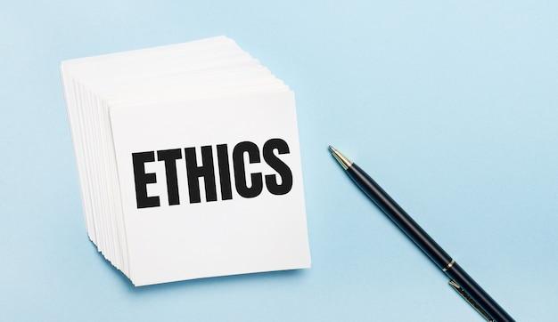 Na jasnoniebieskiej powierzchni znajduje się czarny długopis i stos białych karteczek z napisem etyka