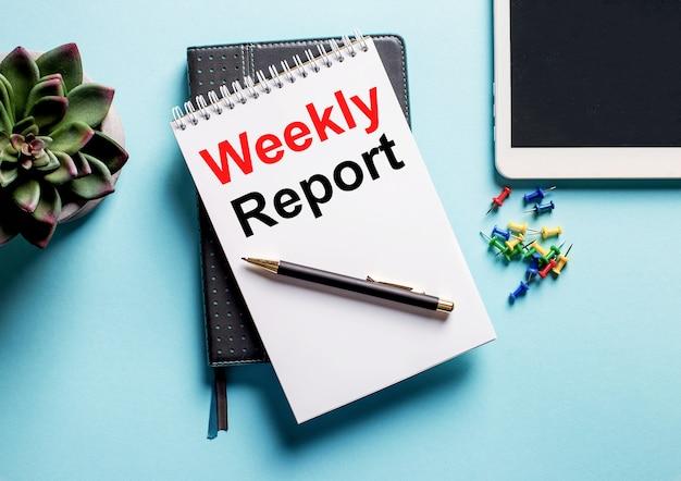 Na jasnoniebieskiej powierzchni znajduje się roślina doniczkowa, tabletka i tygodnik z tekstem raport tygodniowy