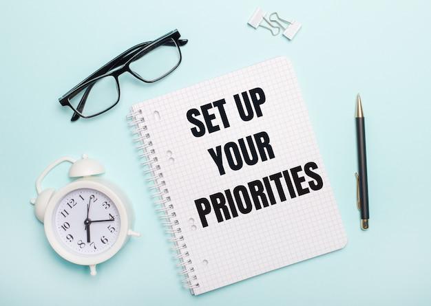 Na jasnoniebieskiej ścianie leżą czarne okulary i długopis, biały budzik, białe spinacze do papieru i notes z napisem ustaw swoje priorytety. pomysł na biznes