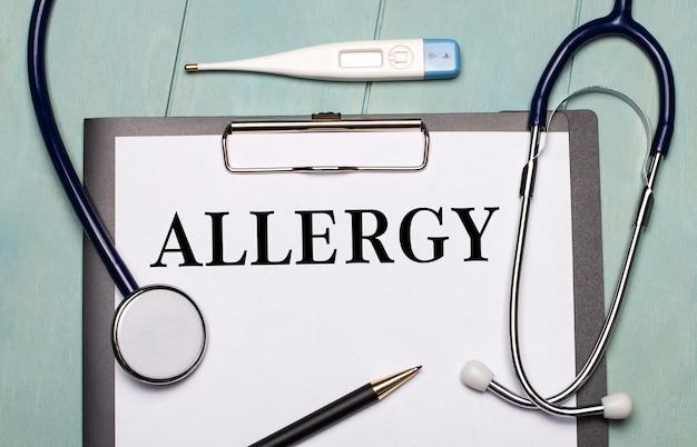 Na jasnoniebieskim drewnianym tle papier z napisem alergia