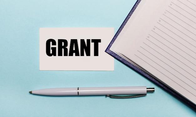 Na jasnoniebieskim stole otwarty zeszyt, biały długopis i karteczka z napisem grant. widok z góry