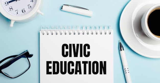 Na jasnoniebieskim tle biała filiżanka z kawą, biały budzik, biały długopis i notes z napisem edukacja obywatelska. widok z góry