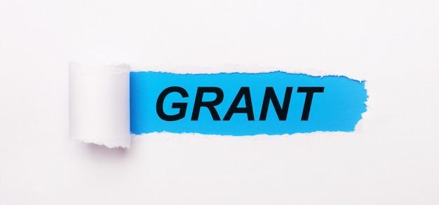 Na jasnoniebieskim tle biały papier z rozdartym paskiem i napisem grant
