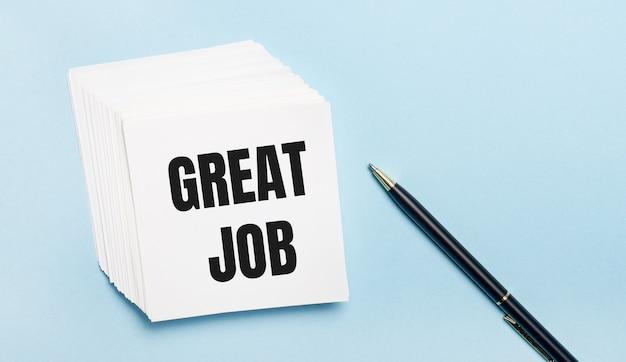 Na jasnoniebieskim tle czarny długopis i stos białego papieru firmowego z napisem great job