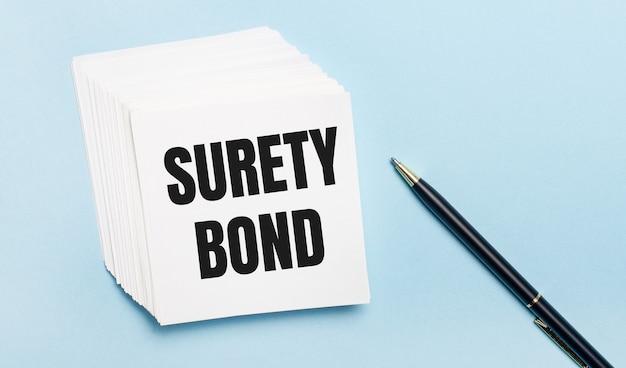 Na jasnoniebieskim tle czarny długopis i stos białego papieru firmowego z napisem surety bond
