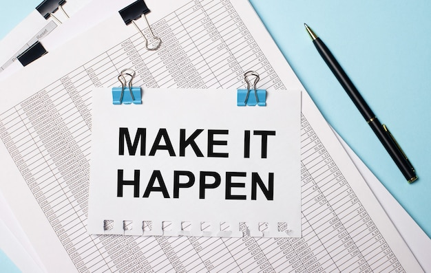 Na jasnoniebieskim tle dokumenty, długopis i kartka na niebieskich spinaczach z napisem make it happen. pomysł na biznes.