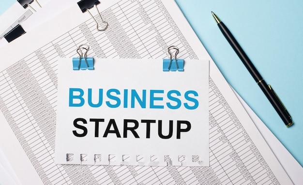 Na jasnoniebieskim tle dokumenty, długopis i kartka papieru na niebieskich spinaczach z napisem business startup. pomysł na biznes.