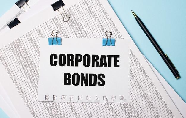 Na jasnoniebieskim tle dokumenty, długopis i kartka papieru na niebieskich spinaczach z napisem corporate bonds. pomysł na biznes.