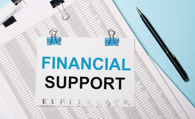 Na jasnoniebieskim tle dokumenty, długopis i kartka papieru na niebieskich spinaczach z napisem financial support. pomysł na biznes.