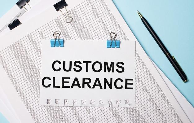 Na jasnoniebieskim tle dokumenty, długopis i kartka papieru na niebieskich spinaczach z napisem odprawa celna. pomysł na biznes.