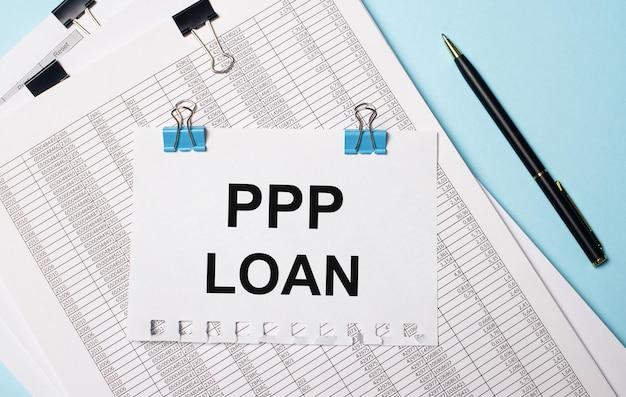 Na jasnoniebieskim tle dokumenty, długopis i kartka papieru na niebieskich spinaczach z napisem ppp loan. pomysł na biznes.