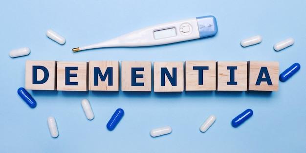Na jasnoniebieskim tle elektroniczny termometr, biało-niebieskie tabletki i drewniane kostki z napisem dementia. koncepcja medyczna