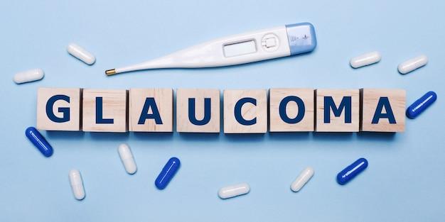Na jasnoniebieskim tle elektroniczny termometr, biało-niebieskie tabletki oraz drewniane kostki z napisem glaucoma. koncepcja medyczna