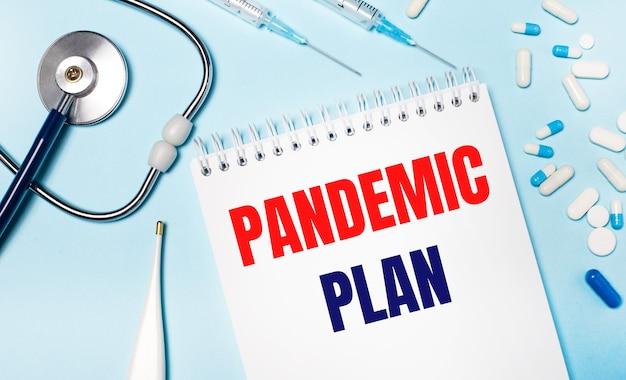 Na jasnoniebieskim tle elektroniczny termometr, stetoskop, biało-niebieskie tabletki, strzykawki i notes z napisem plan pandemii. koncepcja medyczna