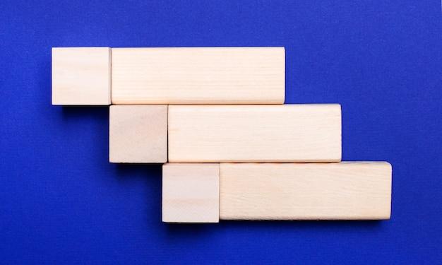 Na jasnoniebieskim tle jasne drewniane klocki i kostki z miejscem na wstawienie tekstu.
