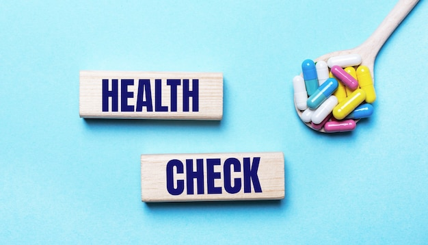 Na jasnoniebieskim tle jasne wielokolorowe tabletki w łyżce i dwa drewniane klocki z napisem kontrola zdrowia. koncepcja medyczna
