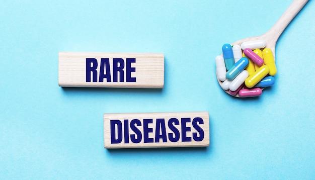 Na jasnoniebieskim tle jasne wielokolorowe tabletki w łyżce i dwa drewniane klocki z napisem rzadkie choroby. koncepcja medyczna