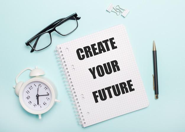 Na jasnoniebieskim tle leżą czarne okulary i długopis, biały budzik, białe spinacze do papieru i notatnik z napisem stwórz swoją przyszłość