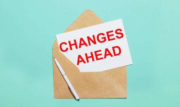 Na jasnoniebieskim tle leży otwarta koperta rzemieślnicza, biały długopis i biała kartka papieru z napisem zmiany do przodu