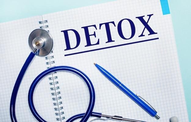 Na jasnoniebieskim tle otwarty notatnik z napisem detox, niebieskim długopisem i stetoskopem. widok z góry. koncepcja medyczna