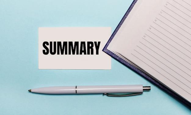 Na jasnoniebieskim tle otwarty notes, biały długopis i kartka z napisem podsumowanie