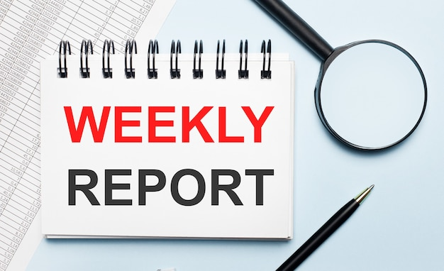 Na jasnoniebieskim tle raporty, lupa, długopis i notes z napisem raport tygodniowy. pomysł na biznes. leżał płasko.