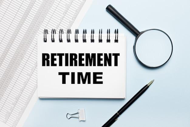Na jasnoniebieskim tle raporty, lupa, długopis i zeszyt z napisem czas emerytury