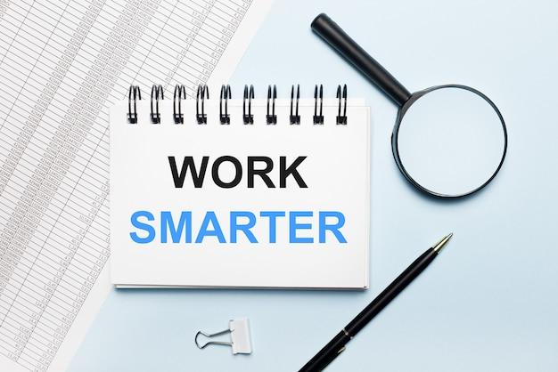 Na jasnoniebieskim tle raporty, szkło powiększające, długopis i notes z napisem work smarter. pomysł na biznes. leżał płasko.