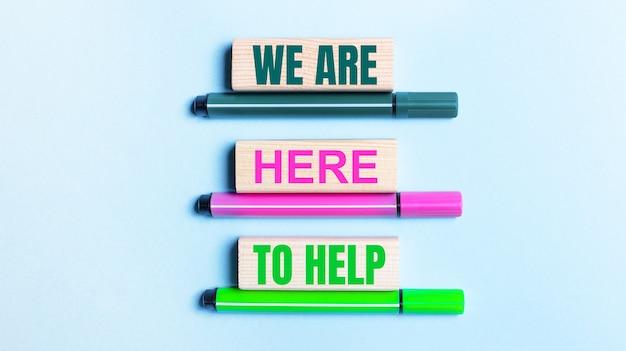 Na jasnoniebieskim tle trzy różnokolorowe flamastry i drewniane klocki z napisem jesteśmy tutaj pomagać.