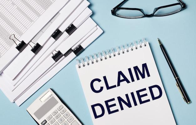 Na jasnoniebieskim tle znajdują się dokumenty, okulary, kalkulator, długopis i notes z napisem claim denied. zbliżenie miejsca pracy. pomysł na biznes