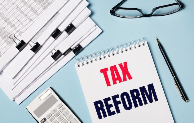 Na jasnoniebieskim tle znajdują się dokumenty, okulary, kalkulator, długopis i notes z napisem tax reform. zbliżenie miejsca pracy. pomysł na biznes