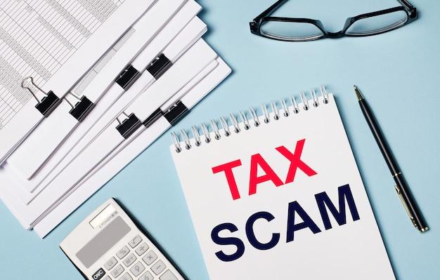 Na jasnoniebieskim tle znajdują się dokumenty, okulary, kalkulator, długopis i notes z napisem tax scam. zbliżenie miejsca pracy. pomysł na biznes