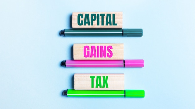 Na jasnoniebieskim tle znajdują się trzy różnokolorowe flamastry i drewniane klocki z podatek od zysków kapitałowych