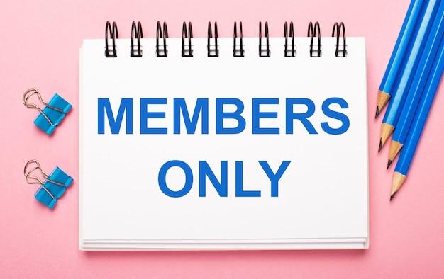 Na jasnoróżowym tle jasnoniebieskie ołówki, spinacze i biały notes z napisem members only