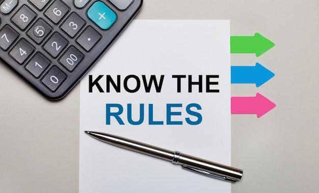 Na jasnoszarej powierzchni kalkulator, biała kartka z napisem znaj zasady, długopis i jasne, wielokolorowe naklejki. widok z góry