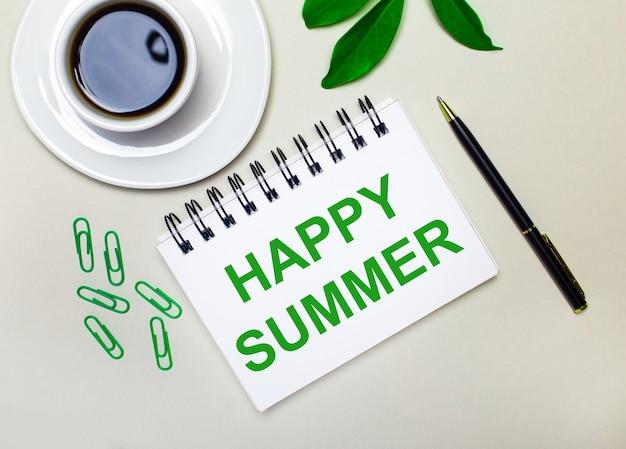 Na jasnoszarym tle biała filiżanka kawy, zielone spinacze i zielony liść rośliny oraz długopis i notes z napisem happy summer.
