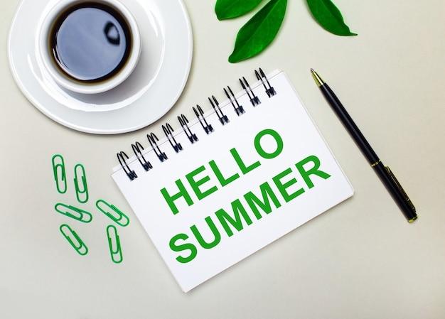 Na jasnoszarym tle biała filiżanka kawy, zielone spinacze i zielony liść rośliny oraz długopis i notes z napisem hello summer.