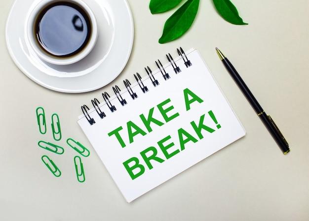 Na jasnoszarym tle biała filiżanka kawy, zielone spinacze i zielony liść rośliny oraz długopis i zeszyt z napisem take a break.