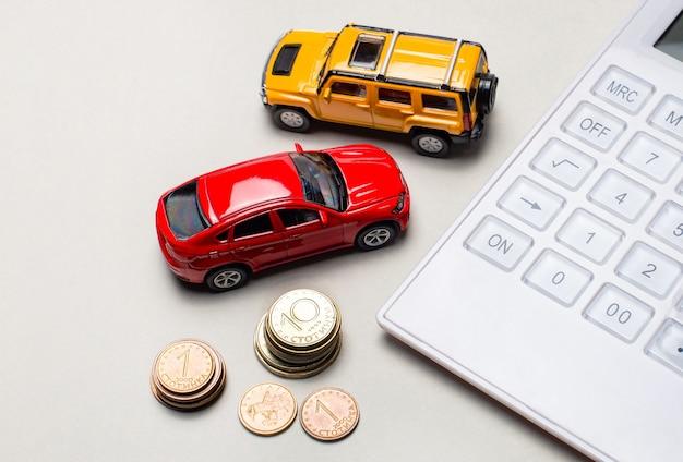 Na jasnoszarym tle czerwono-żółte samochody, biały kalkulator i gotówka.