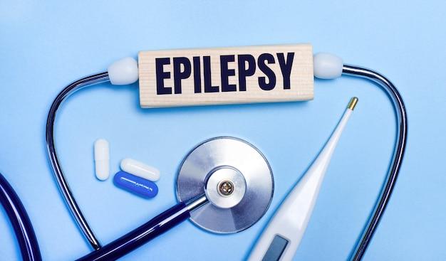 Na jasnoszarym tle stetoskop, termometr elektroniczny, tabletki, drewniany klocek z napisem epilepsja. pojęcie medyczne.