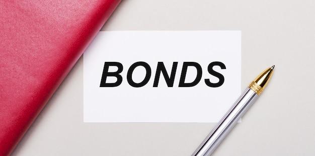 Na jasnoszarym tle widnieje złoty długopis, bordowy notatnik oraz biała czysta kartka z miejscem na wpisanie tekstu bonds. pomysł na biznes. szablon