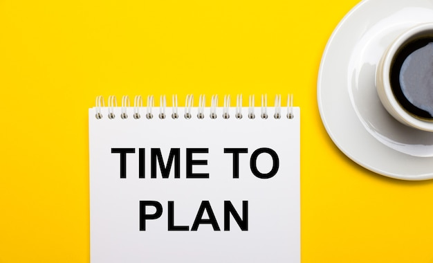Na jasnożółtym tle biały kubek z kawą i biały notes z napisem time to plan